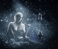 A young woman smoking a hookah on the snow Royalty Free Stock Image