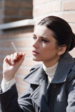 Young woman smoking outside Stock Photo