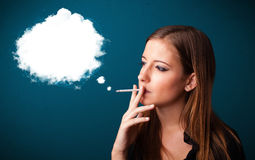 Young woman smoking unhealthy cigarette with dense smoke Royalty Free Stock Images