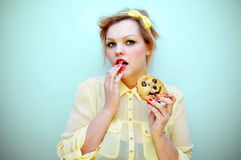 Young woman snacking on a chocolate chip cookie. Stock Images