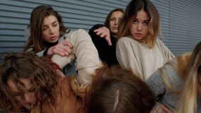 Concepts social danger. A young woman sneaks through the crowd against a striped wall. Female students infringe upon a girl. Concepts social danger or stock footage