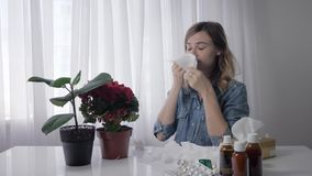 Young woman sneezes, an adult girl is allergic to flowers while sitting at table with medicines and wipes nose with. Young woman sneezes, an adult girl is stock video