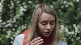 Young woman sneezes and rubs her nose standing near the flowering tree. Allergic rhinitis person. Allergy concept. Young woman sneezes and rubs her nose stock video