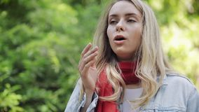 Young woman sneezes and rubs her nose standing on the park background. Allergic rhinitis person. Allergy concept. Young woman sneezes and rubs her nose standing stock video