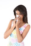 Young woman sneezing. Indian teenage girl with tissue paper Royalty Free Stock Photo