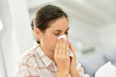 Young woman sneezing and blowing her nose. Young woman with cold blowing her nose Royalty Free Stock Photo
