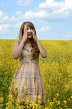 Young woman sneezing at canola field Stock Photo