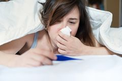 Sick woman blowing her nose lying in bed royalty free stock photo