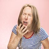 Young woman sneezing, studio portrait. Young funny woman sneezing with spray and small drops, studio portrait on pink background. Comic, caricature, humor stock photos