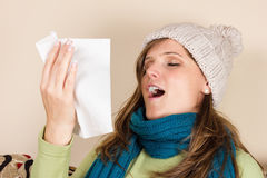 Young woman sneezing in a tissue in the living room, Stock Images