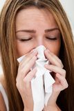Young Woman Sneezing In To Tissue Royalty Free Stock Images