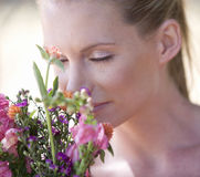A young woman sniffing a bouquet of flowers, close-up Stock Photo