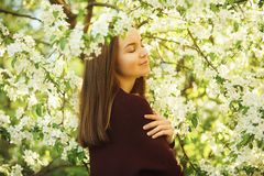 Young woman sniffs a blossoming tree. beautiful girl in spring park. Allergy to pollen Stock Image