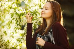 Young woman sniffs a blossoming tree. beautiful girl in spring park. Allergy to pollen Stock Photo