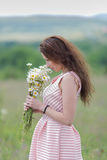 Young woman sniffs bouquet of chamomile on open air Stock Photo