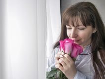 Young brunette woman sniffs a bouquet of roses standing by the window stock photography