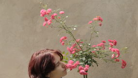 Young woman sniffs roses stock footage
