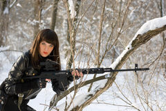 Young woman with a sniper rifle. Portrait of pretty young woman with a sniper rifle in winter forest Royalty Free Stock Photos
