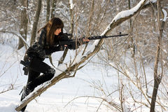Young woman with a sniper rifle. In winter forest Stock Photo