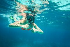 Young woman snorkel, holding two thumbs up stock photos