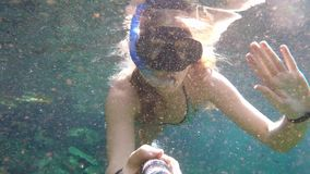 Young woman snorkeling in clear blue water.