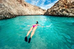 Young woman snorkeling in clear tropical water. Traveling, active lifestyle concept. Watersports on vacation Royalty Free Stock Image