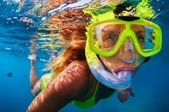 Young woman snorkeling with coral reef fishes. Happy girl in snorkeling mask dive underwater with tropical fishes in coral reef sea pool. Travel lifestyle, water stock photography
