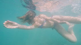 Young woman snorkeling in the tropical sea. Girl in bikini swimming with mask underwater. slow motion. stock video footage