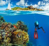 Young woman snorkling next to tropical island. Anchoring catamaran on background royalty free stock image