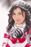 Young woman in snow. A young brunette woman dressed in warm winter clothes, covered in snow Stock Photography