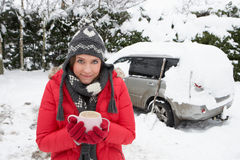 Young woman in snow with car stock photography