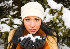 Young woman with snow in hands stock photo