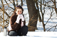 Young woman in snow with thermos bottle Stock Photography