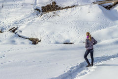 Young woman on snow. Young woman walking on a footpath in the snow Royalty Free Stock Photo