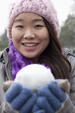 Young Woman with Snowball, Looking At Camera Stock Photography