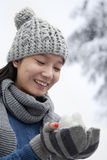 Young Woman with Snowball, Looking Down and Smiling Stock Photo