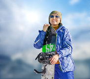 Young woman with snowboard on the bright blue sky background Royalty Free Stock Photography