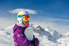 Young woman with snowboard. In ski goggles outdoors with French Alps covered with snow at background. Val-d`Isere, France royalty free stock photo