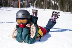 Young happy woman snowboarder lying on a snowy slope. stock image