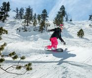 Woman snowboarder in motion in mountains. Young woman snowboarder in motion on snowboard in mountains Royalty Free Stock Photos