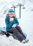 Young woman snowboarder in mountains stock photo