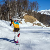 Young woman snowboarder in mountains royalty free stock image