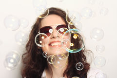 Young woman with soap bubbles. Happy young woman wearing sunglasses with soap bubbles Stock Photo
