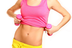 Belly of slim woman with dumbbells on a white background Stock Photo