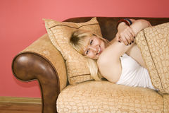 Young Woman on a sofa. Lying down happy blond woman on a couch stock photo