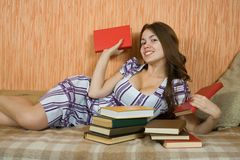 Young  woman  on sofa with books Royalty Free Stock Image