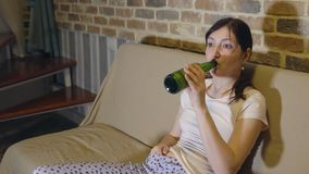 Young woman on sofa in front of TV drinking beer.  stock images