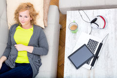 Young woman on the sofa with Gadgets Stock Photo