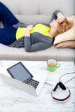 Young woman on the sofa with Gadgets Royalty Free Stock Photography