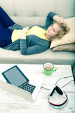Young woman on the sofa with Gadgets Royalty Free Stock Image